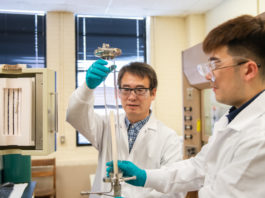 "Jianhua ""Joshua"" Tong, left, and Ph.D. student Shenglong Mu work in their Sirrine Hall lab, where they are working on new technology that combines 3D printing and laser processing."